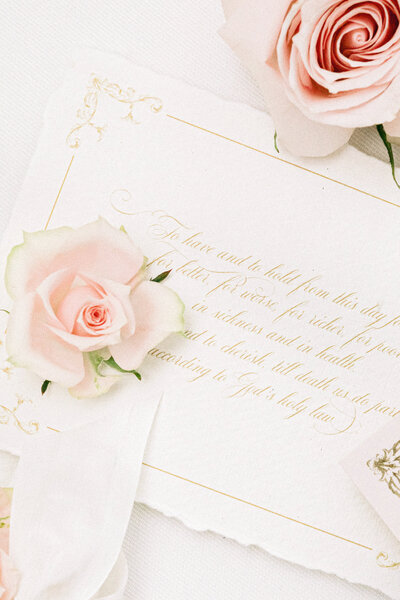 Elegant handwritten vows on parchment surrounded by blush roses
