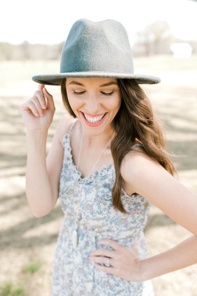 Tia LaRue holds flat brim hat in a blue sundress laughing outdoors