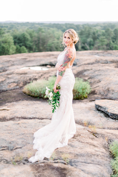 bride with a colorful  sleeve tattoo on a mountain top