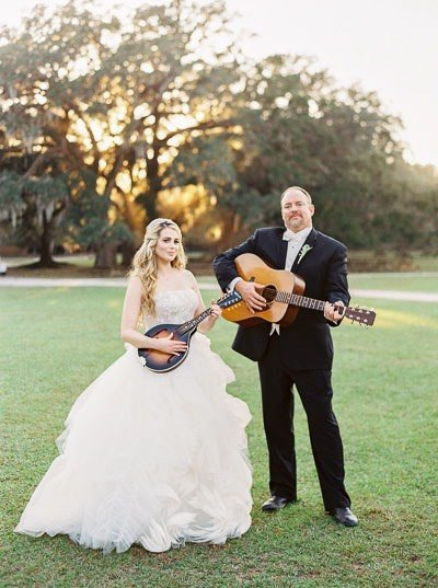 bride and groom playing guitars outside