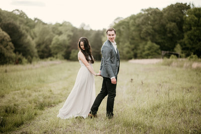Couple walking in a field in their Arkasnas Engagement Session