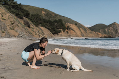 woman bending down to pet dog while on beach with ocean in the background
