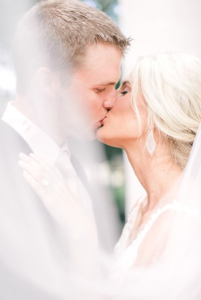 couple sharing a kiss through veil