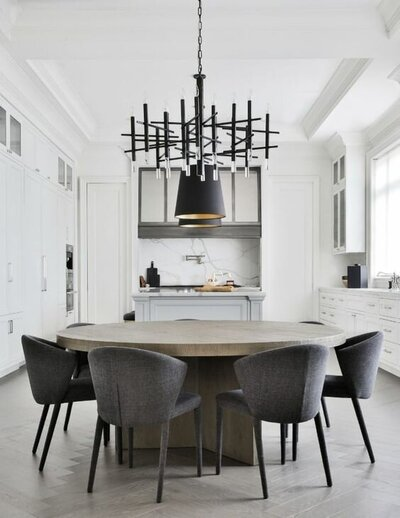 bleached round oak dining table with grey dining chairs with a black geometric Modern chandelier