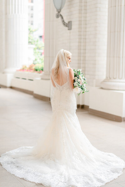 back of bride at her bridal session at dallas union station holding bouquet by dallas wedding photographer catie ann photography