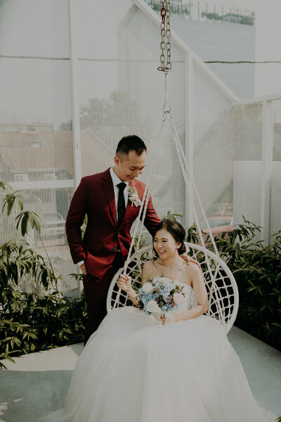 bride sit on swing and groom standing