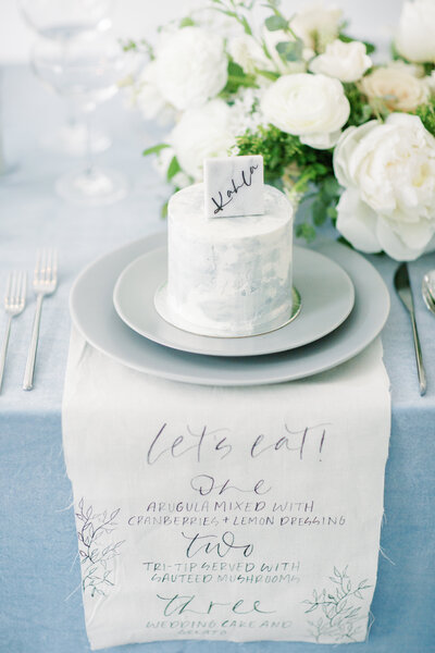 Reception table setting with small guest cake and customized wedding naptkins