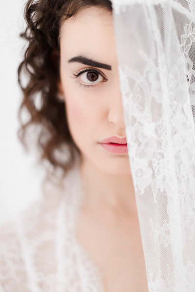 girl's face half obscured by white lace