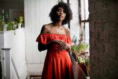 black woman with red dress and plants