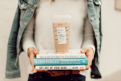 Business books in a stack, being held by Joelle Elizabeht