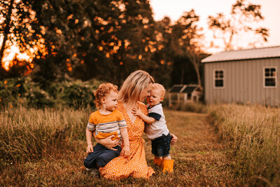 mom of boys with sunset background babies