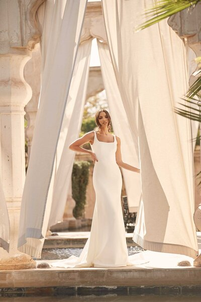 While Aiden is simple she's far from boring – fitted throughout the bodice she flares from the knee down with ivory crepe pooling into a medium length train. Walking through the dappled sunlight of Marrakech, Aiden proves she is no push-over when it comes to love. Her structured silhouette offers brides an intriguing squared-off neckline which tapers into thin straps. But it's when Aiden turns, her bare back emulates the tapered, square structure, but un-like previous designs, Aiden dips even lower for the on-trend brides-to-be.  As the desert temperatures cool in Marrakech, or on a sunset drenched beach, Aiden offers brides an alternative look. Slip into a whisper thin sheer jacket featuring delicate pearls scattered across the bodice and over the draping shoulder sleeves. The back remains open while the high neck accentuates the dress' simple elegance. Brides have the option to explore two different looks on their big day, with the detachable jacket included with the irresistible gown that is Aiden.