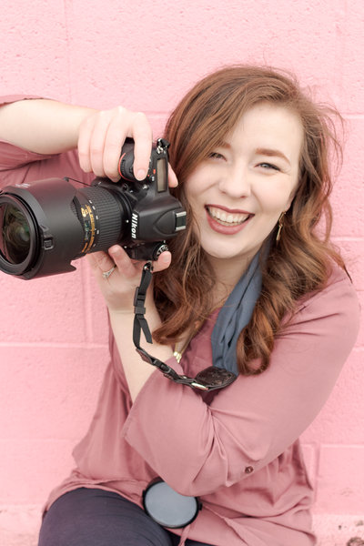 Me with my camera, wearing pink sitting outside a wall in Provo Utah Wedding Photographer
