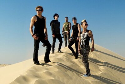 Band portrait My Darkest Days five members standing in V formation on top of sand dune