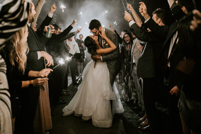 bride and groom kissing while surrounded by wedding guests holding sparklers