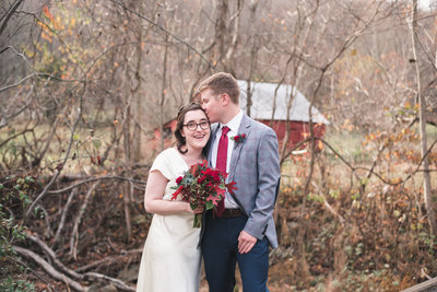 Bride and groom at their rustic mountain wedding with little red barn