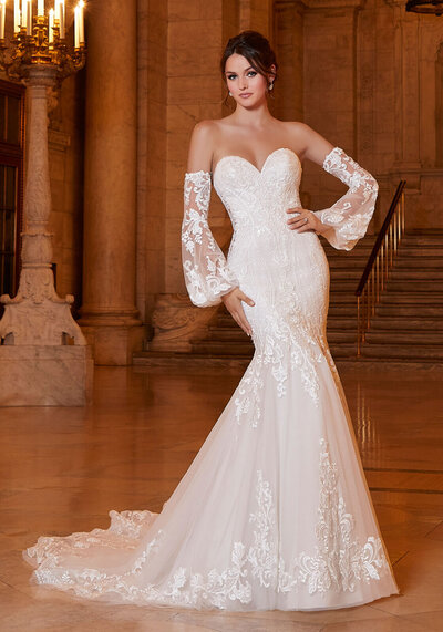 A perfect blend of classic and romantic, the Avonlea designer wedding dress features frosted, medallion style and geometric embroidery that create a beautiful shape on the Net mermaid silhouette. Detachable bishop sleeves add a touch of trend and provide the option of two looks in one. A gorgeous scalloped train edged in lace completes the look. Beaded Spaghetti Straps also included. Available in three lengths: 55″, 58″, 61″. Shown in Ivory/Sand Honey.