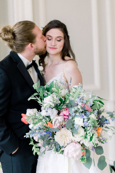 Groom kissing bride with colorful bouquet