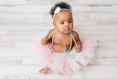 1 year old girl sits in tutu and pearls with bow in her hair