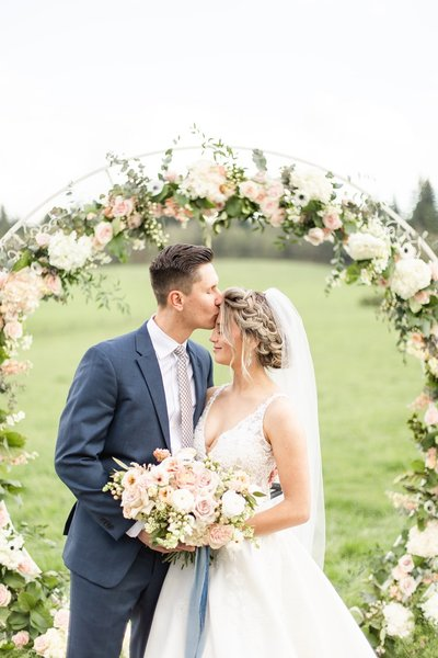 groom kissing bride's forehead while she holds her bouquet and stands in front of a floral arch
