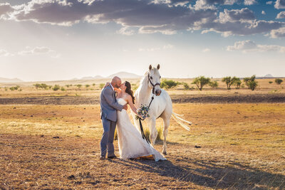 country western bride and groom kissing in front of their white horse
