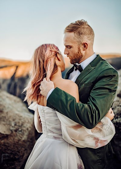 Magical engagement photoshoot at Glacier point in Yosemite . Fairytale and sunrise. Winter in Yosemite . Bridal dress and men attire. Photos around rock. Couples posing photoshoot . Pink hair. Dreamy styling shoot .