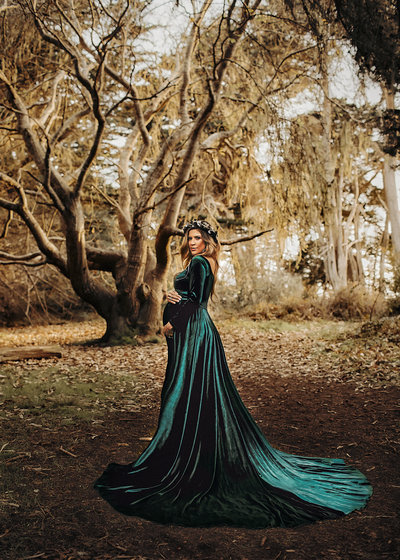Outdoor glamorous maternity session in the middle of trees and florest as a fairytale dream. Velvet dress. Flower crown. Mother nature.