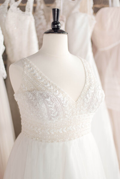 Plus size glam wedding dress on mannequin in bridal boutique