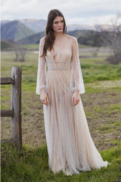 Faceted stones sparkle like raindrops all over our dreamy illusion tulle Lunella. Finished with full long sleeves, it's a natural wonder brought to life in the guise of a gown.