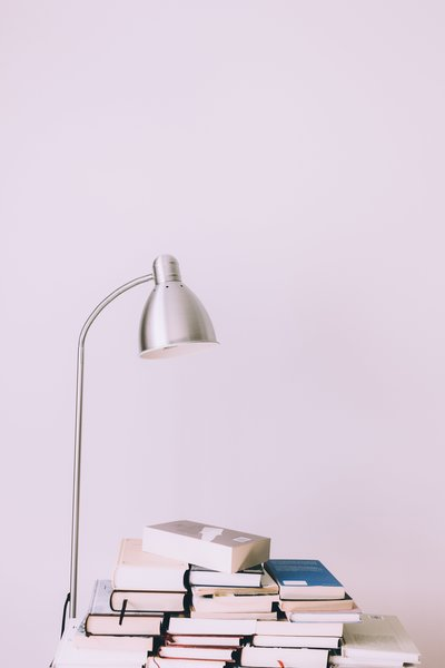 silver-desk-lamp-near-pile-of-books-1122530