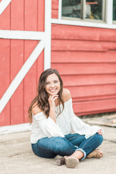 Cute teen sitting cross legged in front of a red barn door.