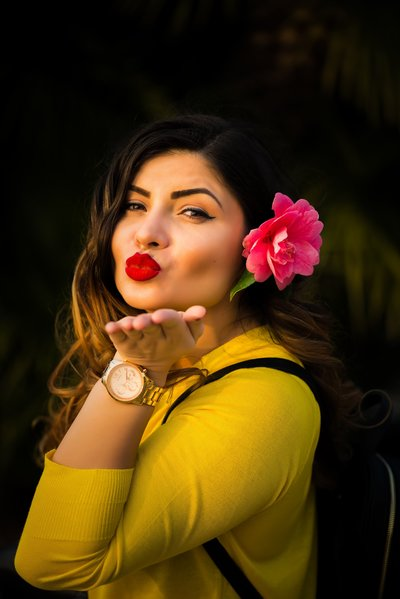 pretty latina with red lipstick blowing a kiss