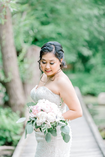 bride standing on the path holding a wedding bouquet