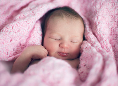 Newborn baby sleeping in pink blanket