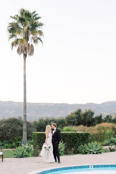 bride and groom kissing by pool at Santa Barbara venue Hidden Oaks by dallas wedding photographer catie ann photography