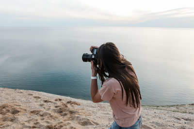 woman taking picture on cliff next to water