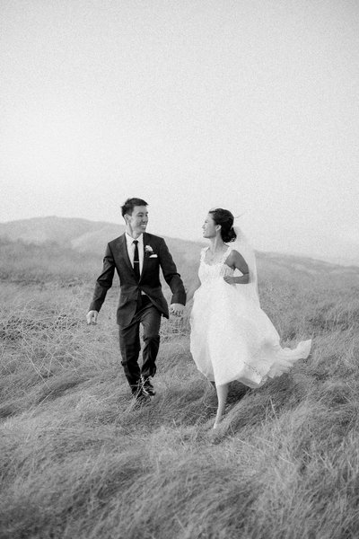 Bride and groom run through a field at their Livermore wedding at Nella Terra Cellars