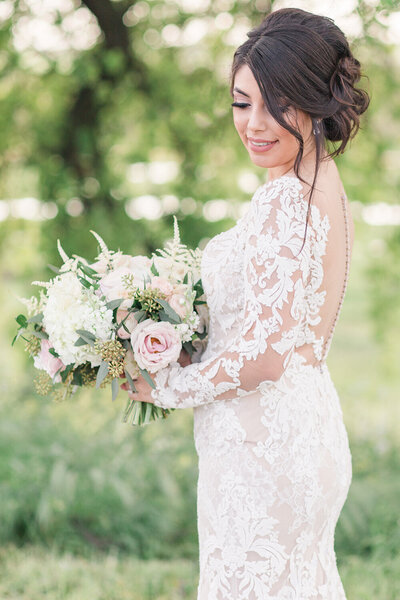A bride poses with her bridal bouquet showing off the back of her wedding gown at her California winery wedding.