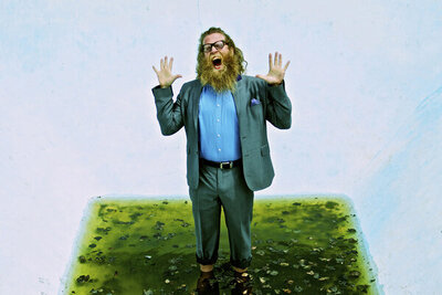 Musician portrait Ben Caplan standing in puddle in drained pool holding up his arms and screaming