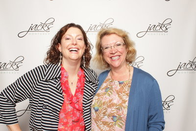 two ladies smiling for step and repeat