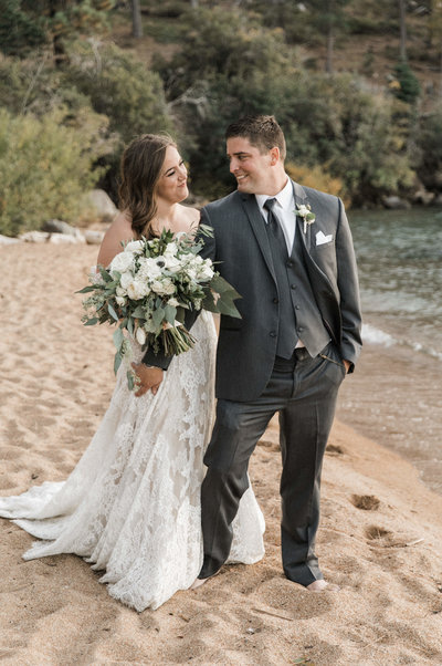 bride and groom walking next to water
