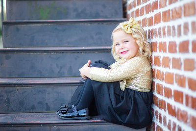 A little girl sits on a stairway and smiles in Wauchula, Florida.