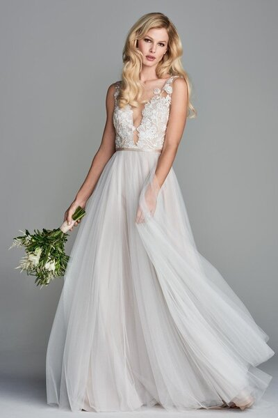 Juno's deep V-neck illusion bodice is covered in a floral lace motif, complete with an option of functional covered buttons or a zipper with non-functional covered buttons in the back. An A-line skirt composed with layers of Soft Netting finishes off this romantic gown.