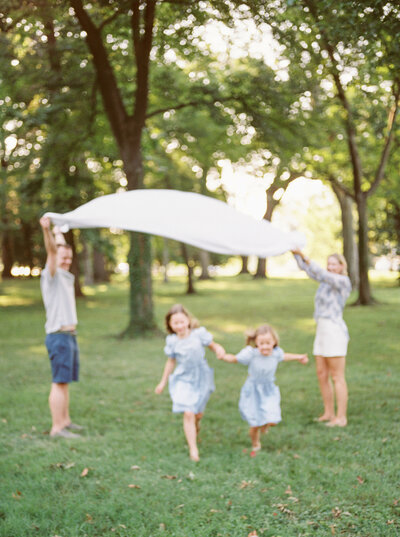Two sisters running underneath blanket thrown in the air by their parents during DC family session.