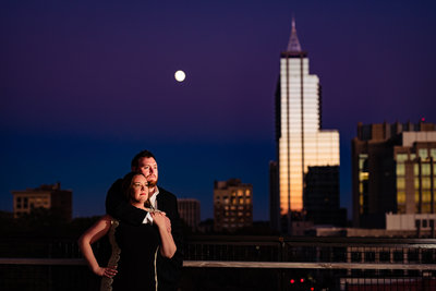 Couple standing in front of downtown Raleigh skyline with a full moon