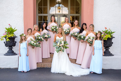 Bride with her bridesmaids in blush pink dresses and flowers pose on the stairs at Ravisloe Country Club.