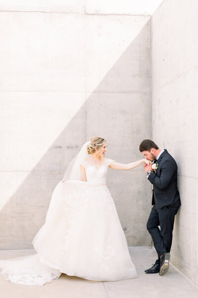 Groom kissing brides hand in downtown phoenix