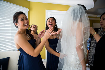 Bridesmaids interact with the photographer while the bride is getting ready for her wedding.