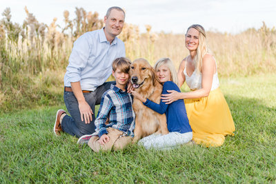 Photographer Amanda Zabrocki smiles with her 2 children, husband, and golden retriever in a field
