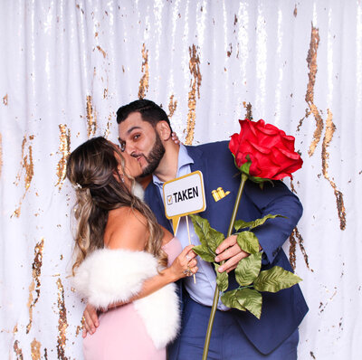 couple kissing with our large rose prop in our photo booth in front of a white and gold backdrop